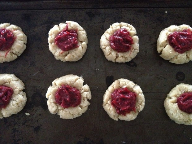 Place a teaspoon of the rhubarb plum jam in the indents of the dough
