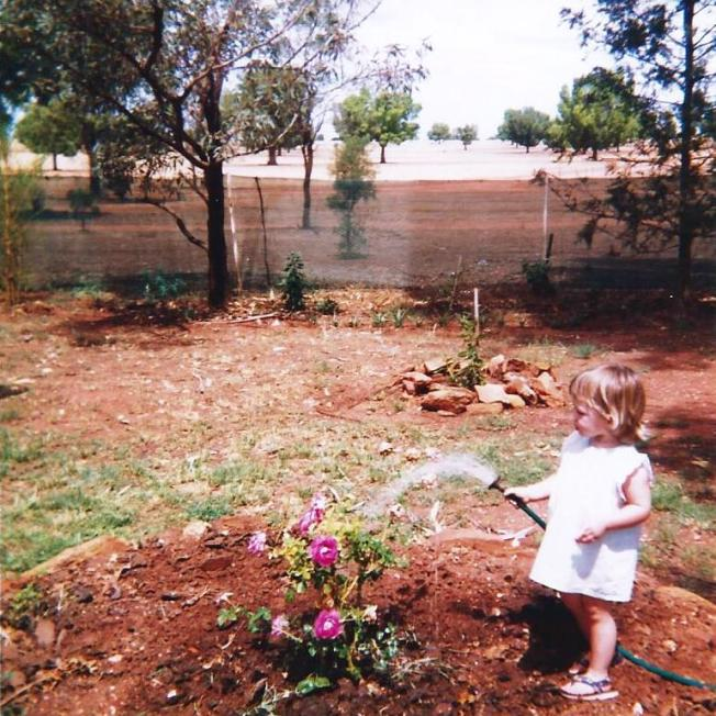 Young girl watering the garden