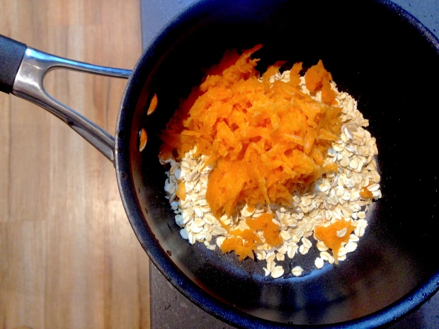 Grated carrot and oats in a saucepan on the stove